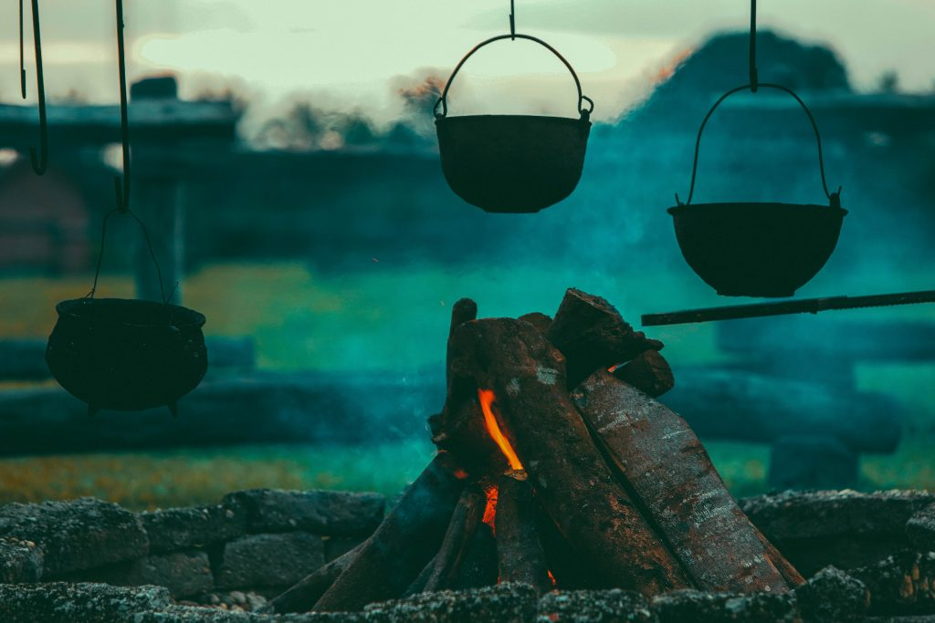 Three hanging pots by a fire pit.