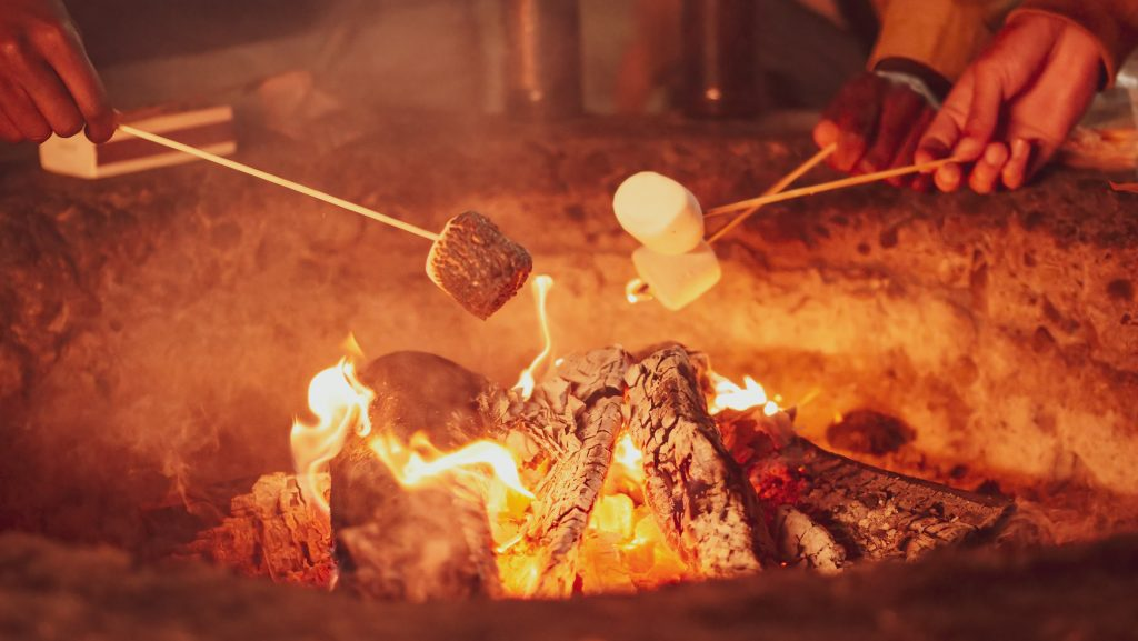 Roasting marshmallows by fire.