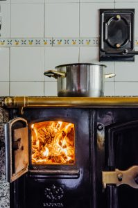 Wood stove with silver casserole.