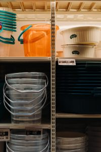 Plastic buckets in a shelf.