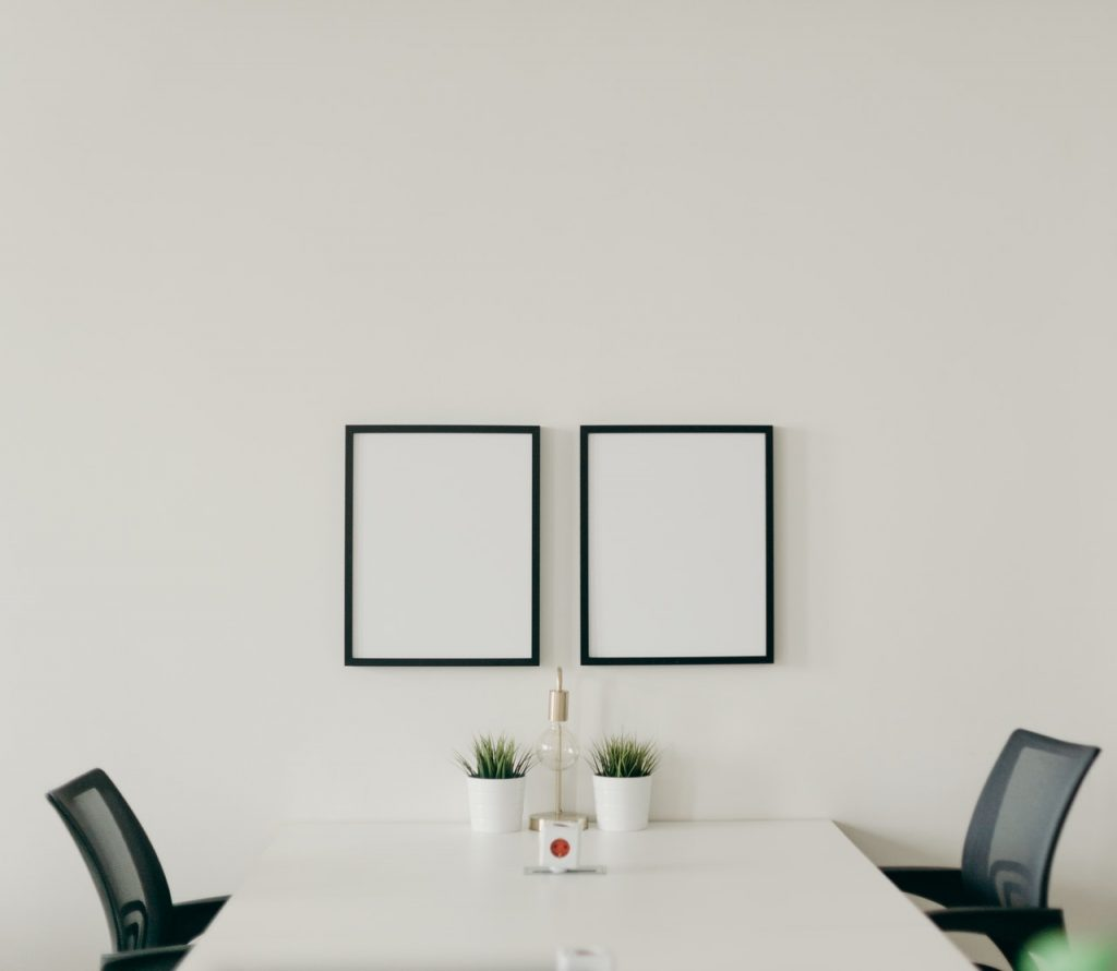 White room with chairs and frames.