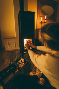 Woman heating by a stove.