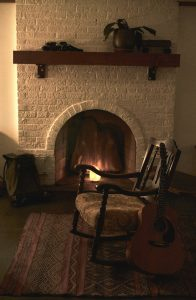 Chair and guitar by a fireplace.
