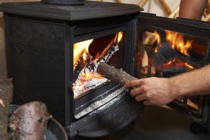 Man adding wood in stove.