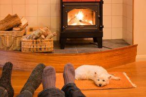 Socked feet and dog by wood burning stove.