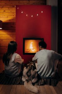 Couple and dog by fireplace.