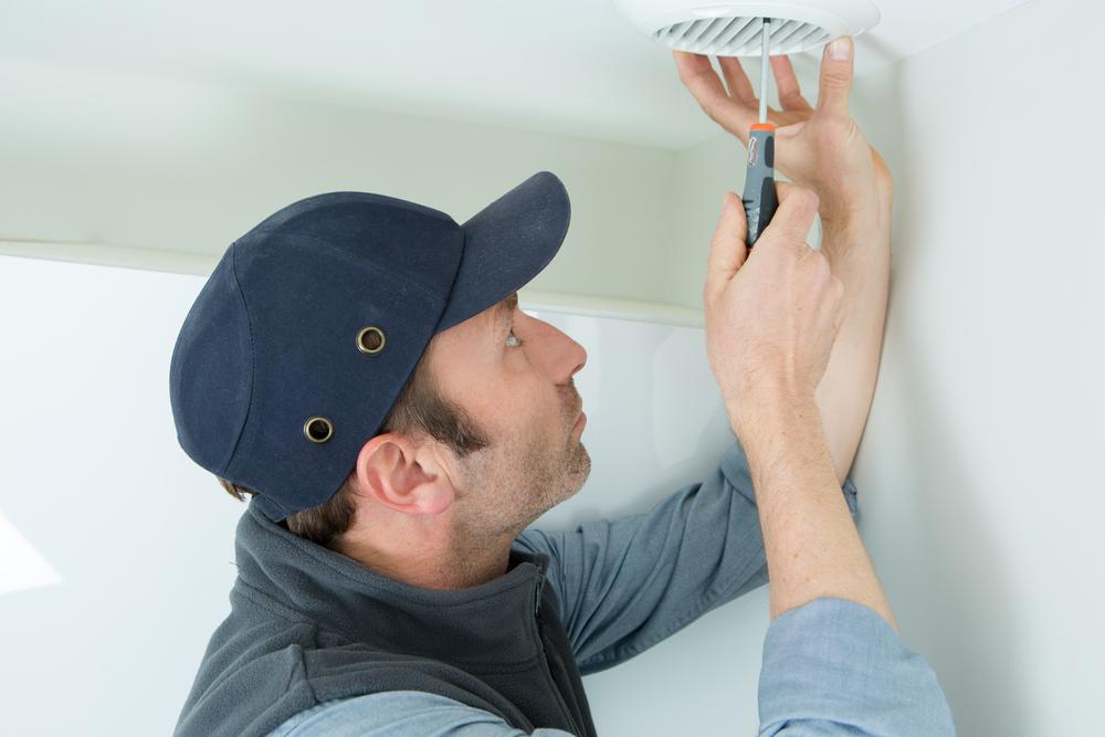 Man doing bathroom exhaust fan installation.