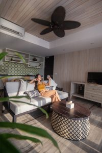 Woman in living room with ceiling fan.